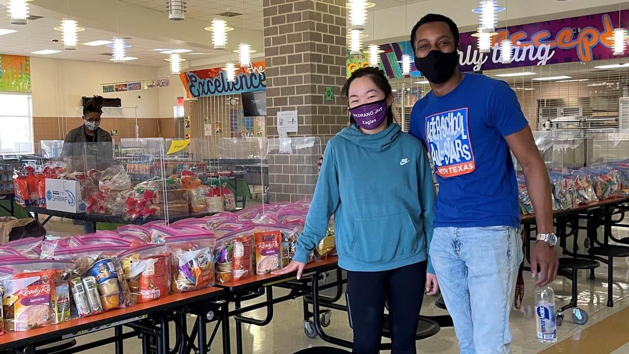 Volunteers standing in front of food drive table